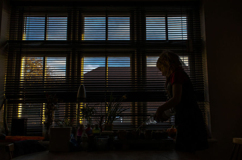 Woman pouring drinking water at dining table by window