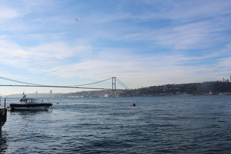 Boats in sea by bosphorus bridge against cloudy sky