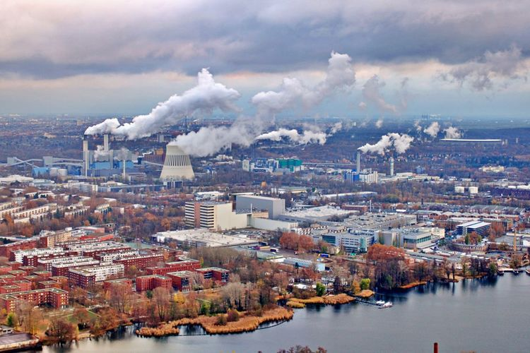 Aerial view of smoke and buildings against sky