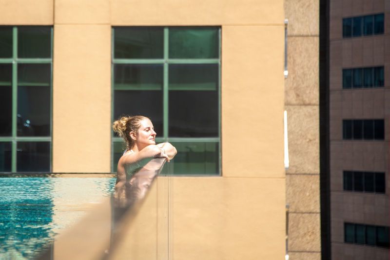 Side view of woman in swimming pool by window