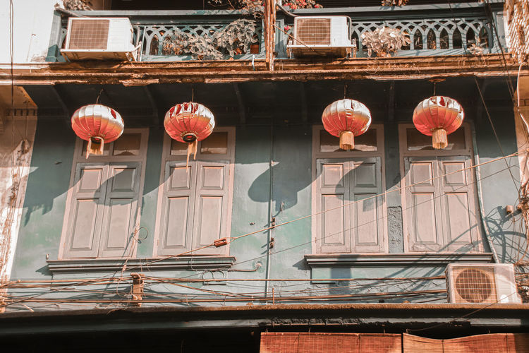 Low angle view of chinese lanterns hanging outside old building