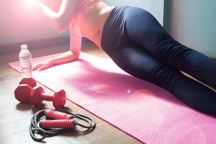 Low Section Of Woman Doing Yoga On Mat