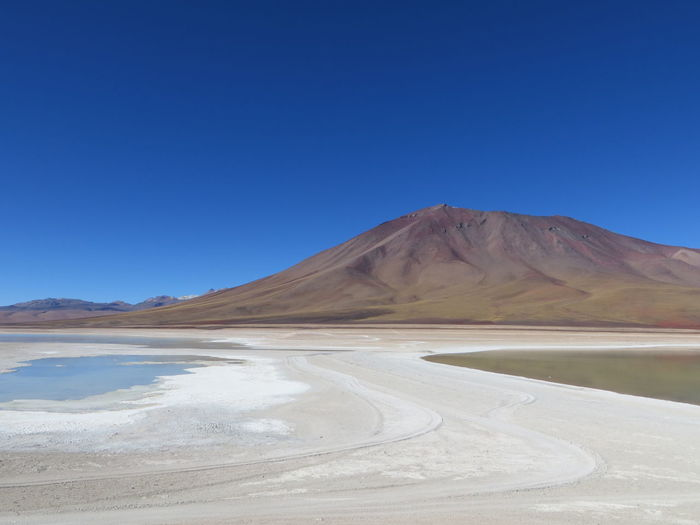 Beauty In Nature Blue Bolivia Clear Sky Coastline Copy Space Lake Majestic Mountain Mountain Peak Natural Landmark Nature Non-urban Scene Outdoors Remote Salt - Mineral Salt Basin Salt Flat Scenics Solitude Tourism Tranquil Scene Tranquility Travel Destinations Water
