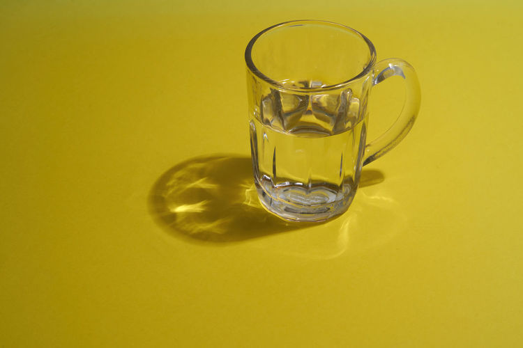 Close-up of yellow glass on table