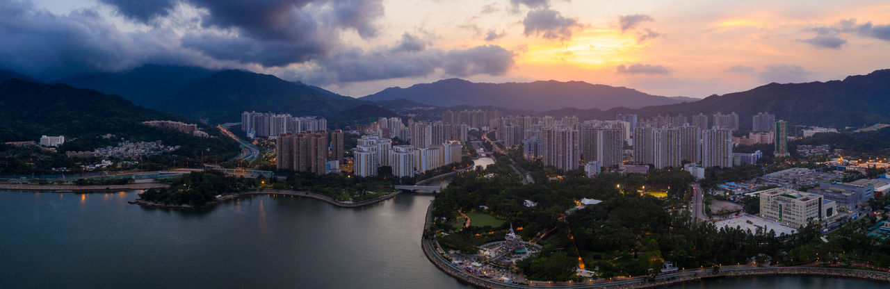 Panoramic view of buildings and mountains against sky at sunset