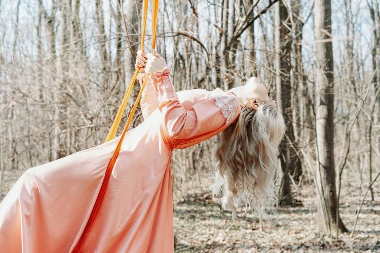 Woman in swing by tree on forest