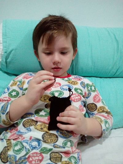 Boy Wearing Pajamas Holding Bag While Lying On Bed At Home