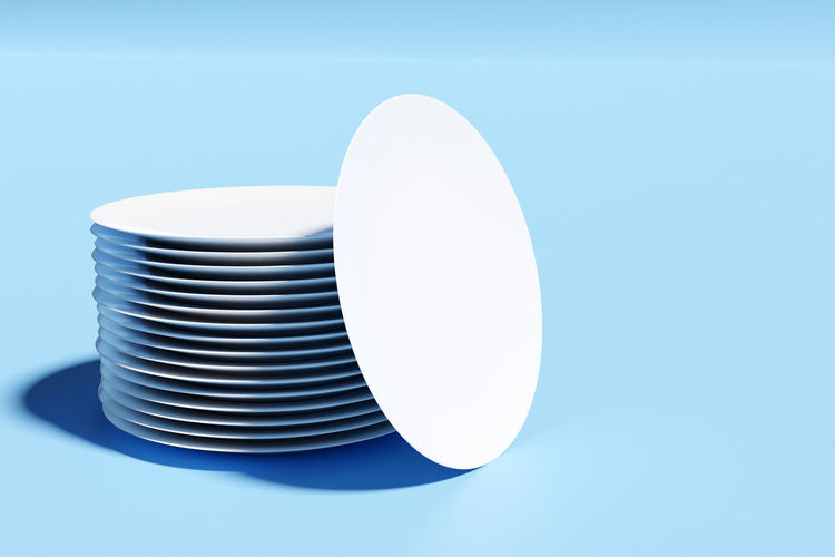 Close-up of white stack on table against blue background