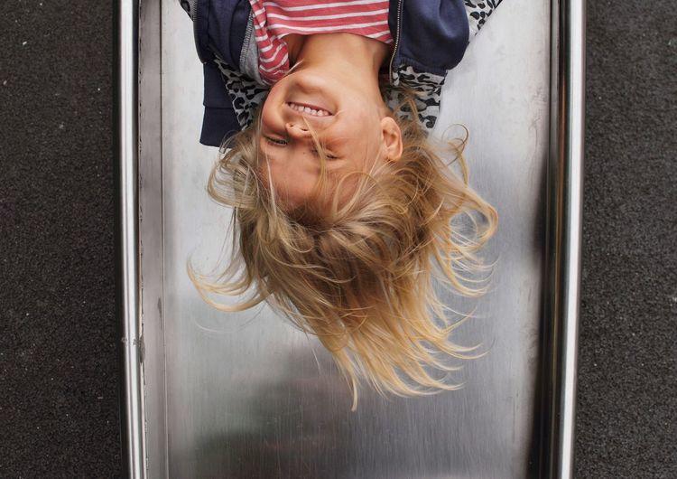 Upside down image of smiling girl enjoying on slide