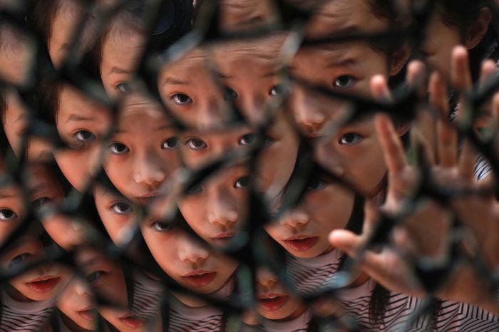 Reflection of cute girl seen in broken mirror pieces