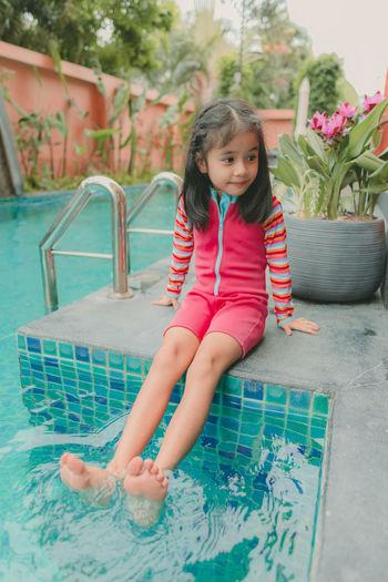 Cute girl sitting in swimming pool