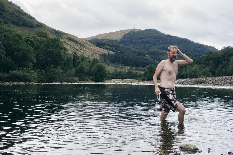 Shirtless man wading in lake against sky