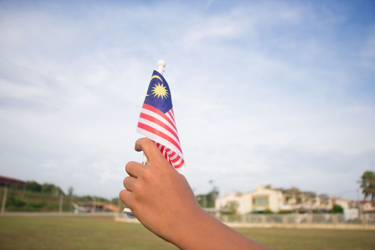 Hand waving Malaysian flag ASIA August Cloud Country Field Independence Life Love Patriotic Patriotism Waving Flag Hand Independence Day Malaysia Merdeka Sky