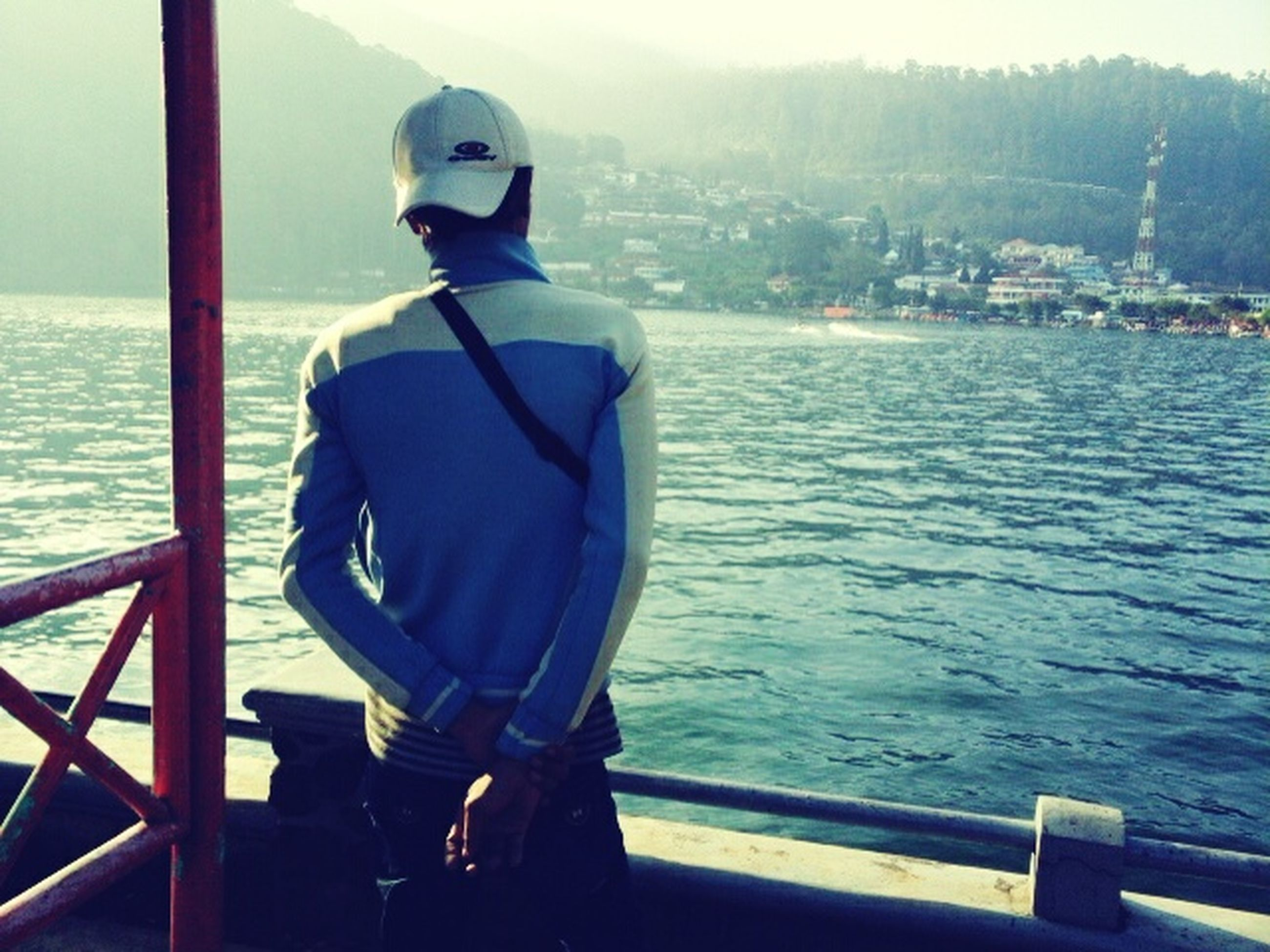 sea, water, railing, rear view, lifestyles, leisure activity, standing, men, nautical vessel, looking at view, day, built structure, casual clothing, pier, sky, three quarter length, sitting, person