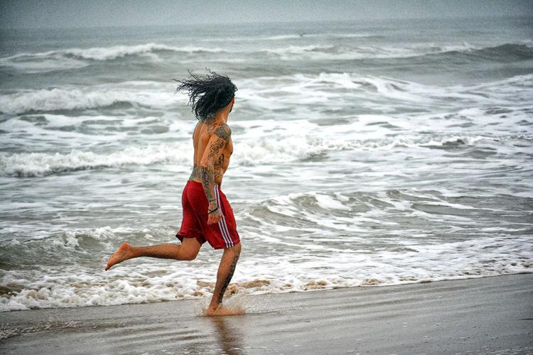 Shirtless man running at sea shore