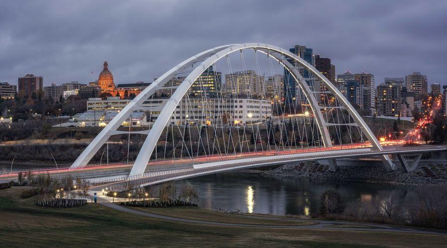 Illuminated bridge over river against buildings in city calgary