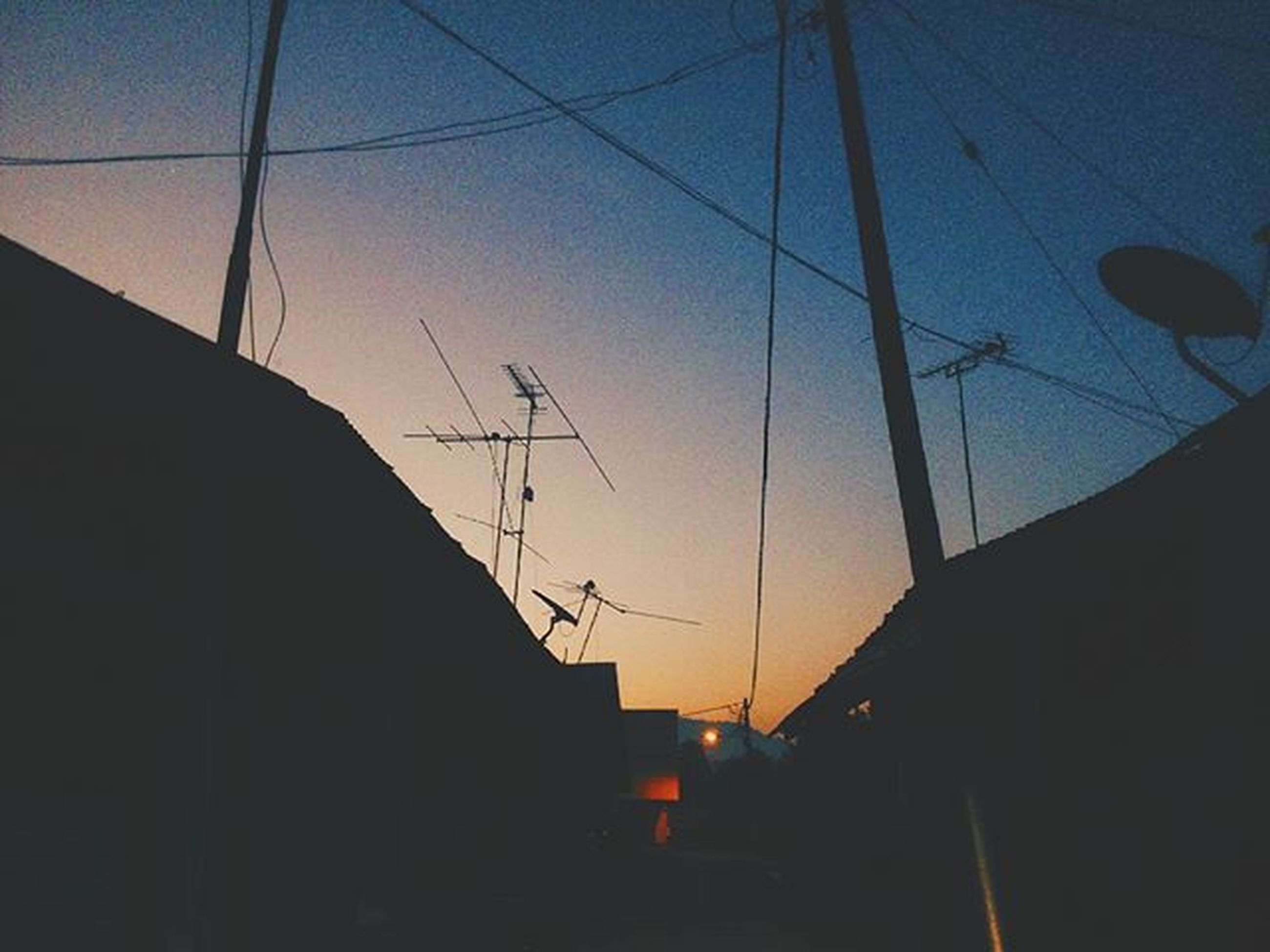 building exterior, built structure, architecture, sunset, power line, silhouette, low angle view, sky, electricity pylon, cable, electricity, house, dusk, transportation, power supply, residential structure, building, outdoors, street light, clear sky