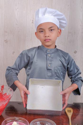 Portrait of boy preparing food in kitchen
