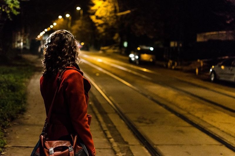 Woman waiting on street at night