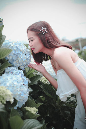 Side view of young woman smelling flowering plant at farm