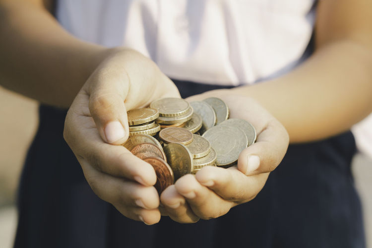 Midsection of girl holding coins outdoors