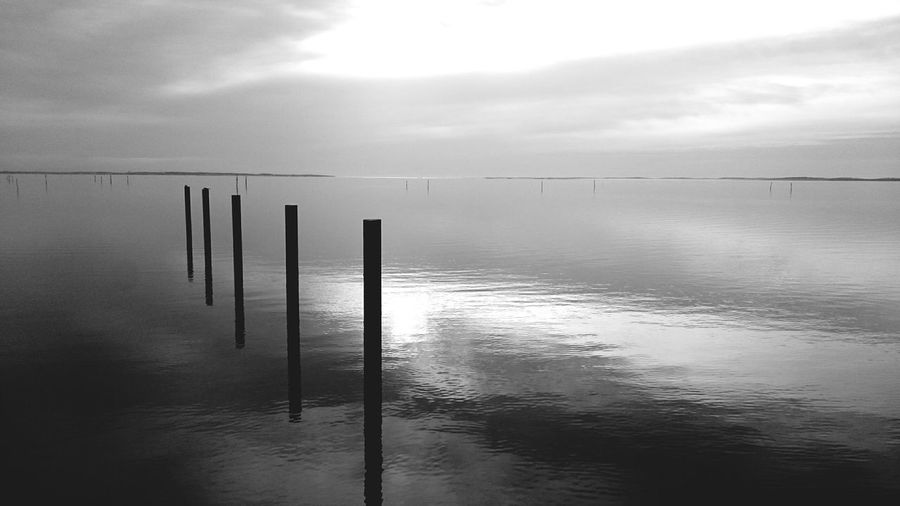 Wooden posts in sea against cloudy sky during sunset