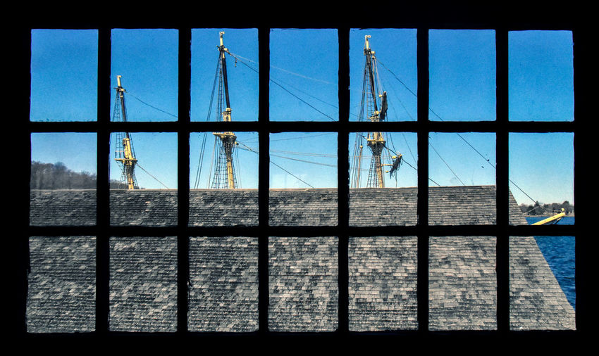 The Joseph Conrad at Mystic Seaport, CT, seen through the windows of the cordage workshop. The iron-hulled fully rigged sailing ship, originally launched as Georg Stage in 1882 and used to train sailors in Denmark. After sailing around the world as a private yacht in 1934 she served as a training ship in the United States, and is now moored at Mystic Seaport in Connecticut. Australian sailor and author Alan Villiers saved Georg Stage in 1934 from the scrappers and renamed the ship in honor of famed sea author Joseph Conrad. Villiers planned a circumnavigation with a crew of mostly boys. Joseph Conrad sailed from Ipswich on 22 October 1934, crossed the Atlantic Ocean to New York City, then down to Rio de Janeiro, Cape Town, and across the Indian Ocean and through the East Indies. After stops in Sydney, New Zealand, and Tahiti, Joseph Conrad rounded Cape Horn and returned to New York on 16 October 1936, having traveled a total of some 57,000 miles (92,000 km). Villiers was bankrupted as a result of the expedition (although he did get three books out of the episode - Cruise of the Conrad, Stormalong, and Joey Goes to Sea), and sold the ship in 1936 to Huntington Hartford, heir to the A&P supermarket fortune, who added an engine and used her as a yacht. In 1939 Hartford transferred the vessel to the Maritime Commission, who used her for training until 1945. After being laid up for two years, the ship was transferred to Mystic Seaport. In addition to her role as a museum, she is also a static training vessel and is employed by Mystic Seaport to house campers attending the Joseph Conrad Sailing Camp. The ship is fully rigged, just on a smaller scale than comparable ships, and this way very handy as a teaching vessel. Architecture Clear Sky Close-up Cordage Workshop. Day Joseph Conrad Lock Masts Metal Mystic Seaport No People Outdoors Security Bar Sky Window Window Frame Windows Workshop Ship Sailing Ship Three Master Sailing Vessel Nautical Vessel Nautical Nautical Scene
