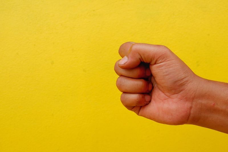 Cropped hand clenching fist against yellow wall