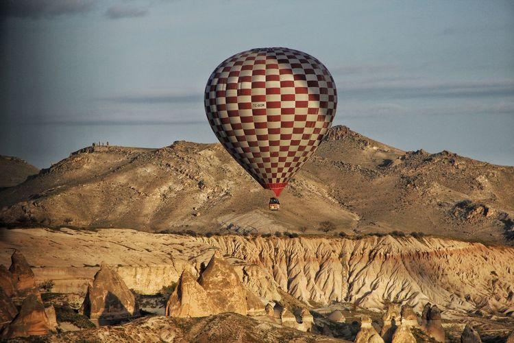 Hot air balloon flying over desert against sky during sunset