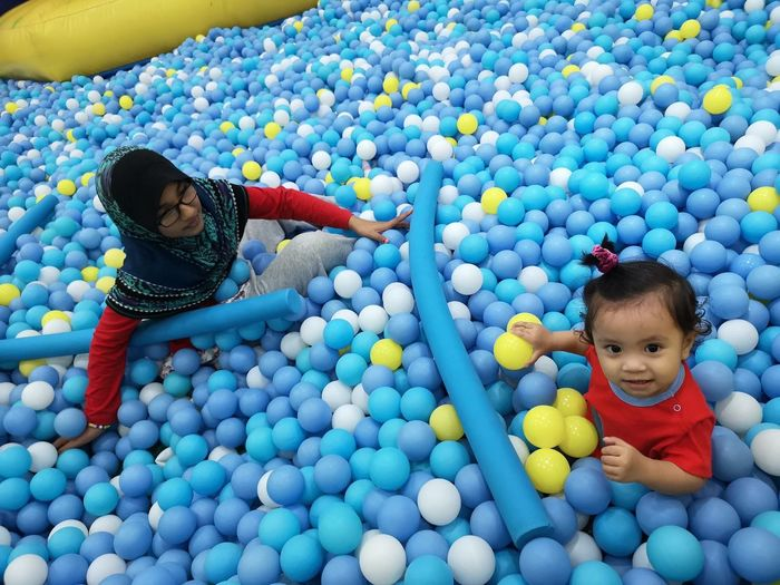 High Angle View Of Sisters In Ball Pool