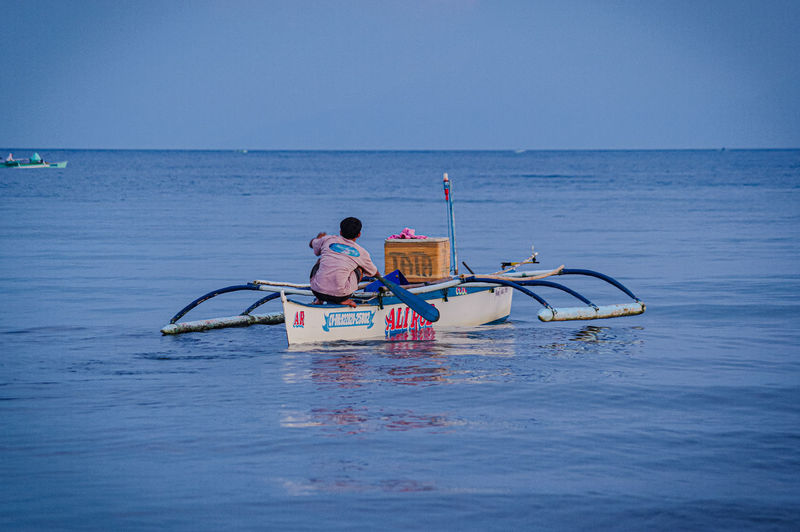 Men on boat in sea against clear sky