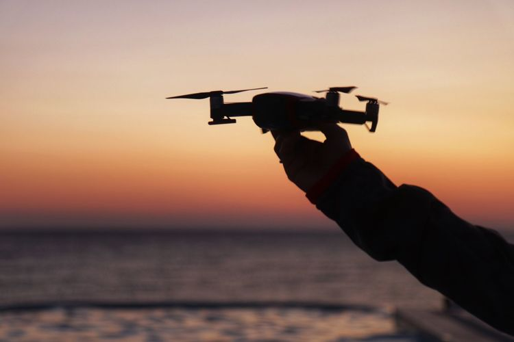 Cropped hand of woman holding drone against sea during sunset