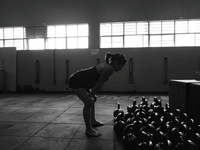 Side view of woman bending by kettlebells in gym