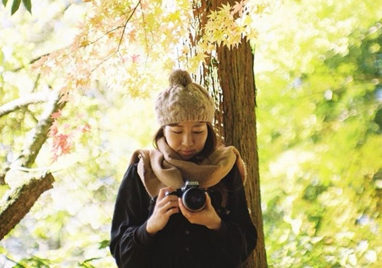 Portrait of man holding camera while standing by tree in forest
