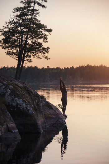 Man on rock by lake against sky during sunset