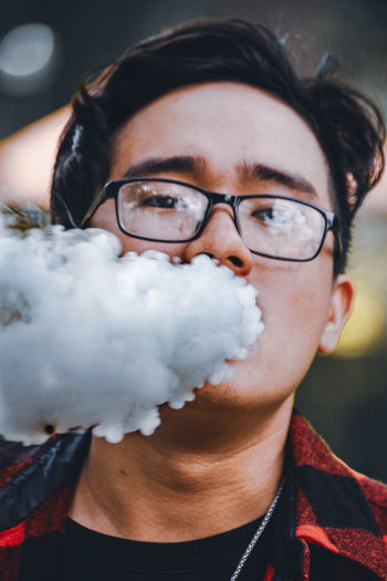 Portrait of man wearing eyeglasses blowing smoke from mouth outdoors