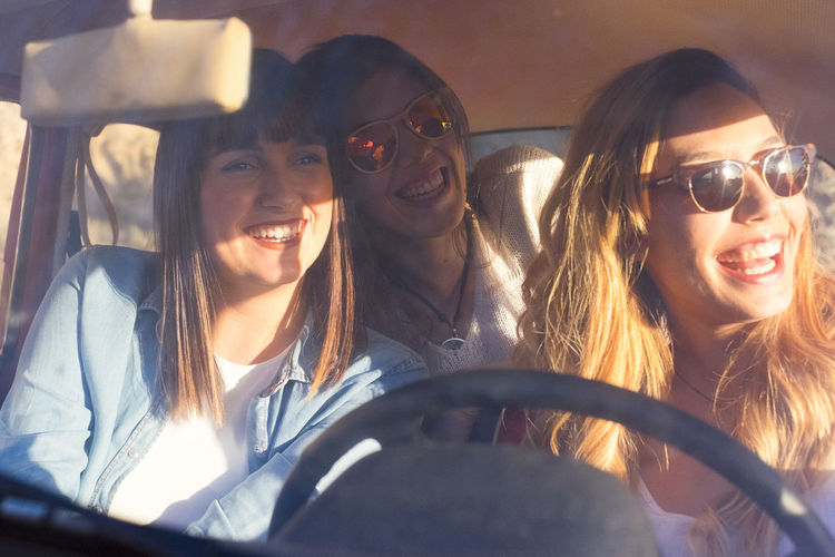 Smiling Friends Sitting In Car