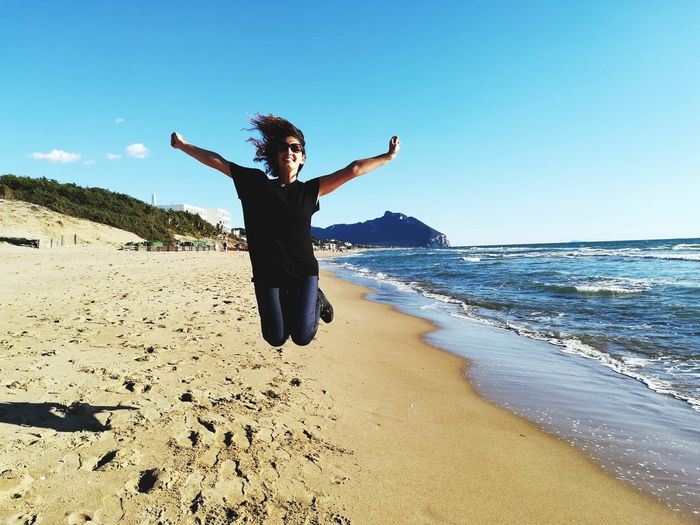 Full length of woman jumping at beach