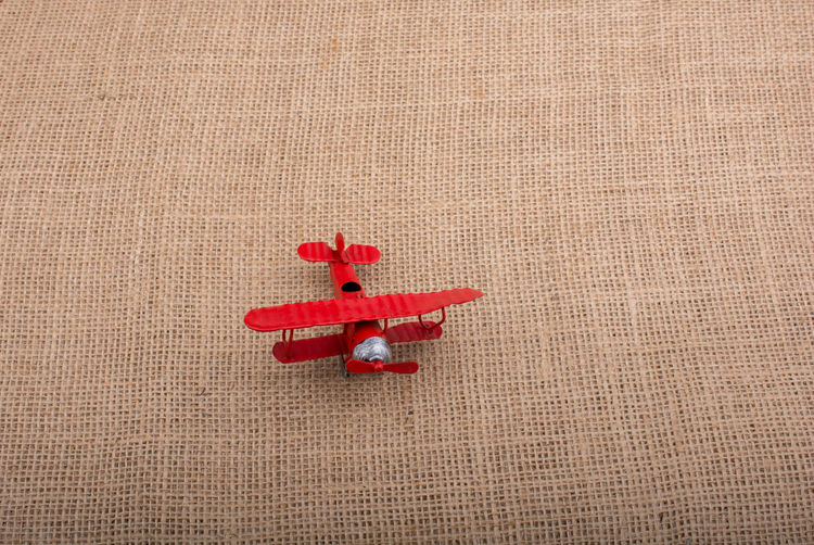 Toy airplane on a linen canvas background Air Vehicle Aircraft Airplane Close-up Day Flight Indoors  No People Pilot Red Travel Destinations Wings