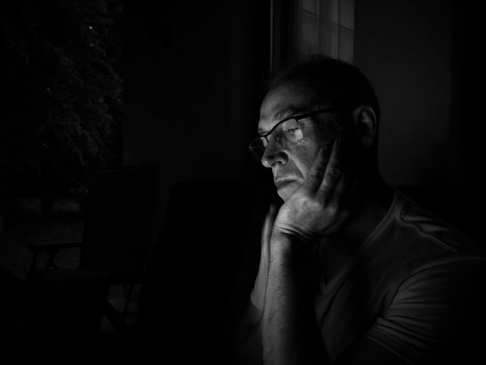 Thoughtful man in darkroom at home