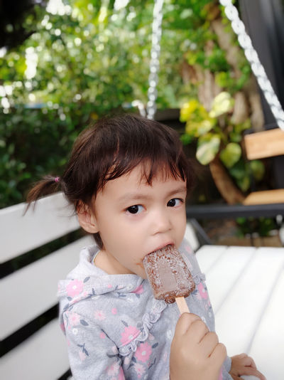 Asian children girl eating ice cream. Child Childhood One Person Real People Innocence Cute Portrait Girls Lifestyles Focus On Foreground Females Looking Leisure Activity Looking Away Headshot Casual Clothing Outdoors Asian  Thai Ice Cream