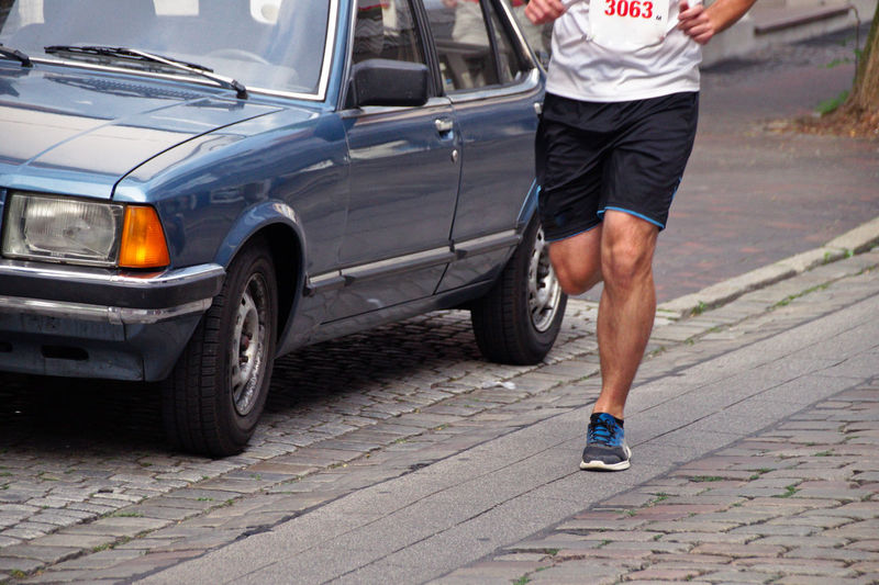 Low section of marathon athlete running by car on street