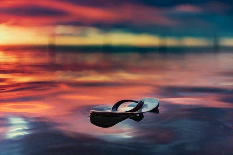 Close-up of sunglasses on beach against sky during sunset