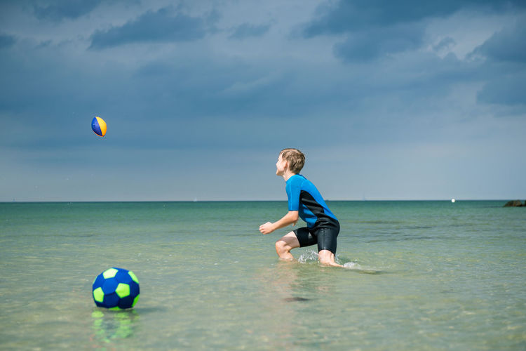 Boy playing with ball in sea against sky