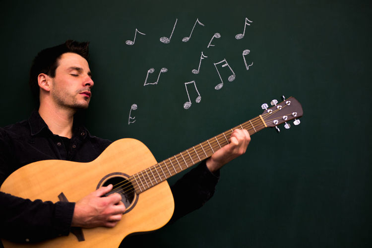 Mid Adult Man With Chalk Drawing On Blackboard Playing Guitar