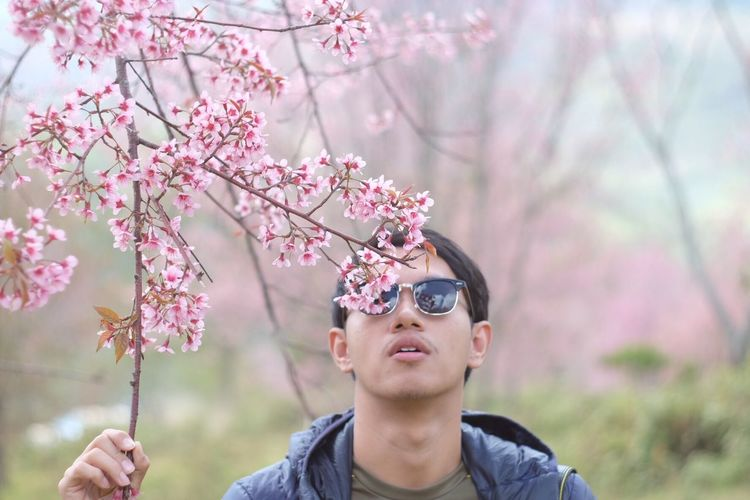 Uniqueness Flower Tree Headshot Outdoors One Person Nature Real People Sunglasses Focus On Foreground Lifestyles Day Leisure Activity Growth Beauty In Nature Childhood Freshness Fragility Close-up Sky Young Adult Phetchabun Thailand