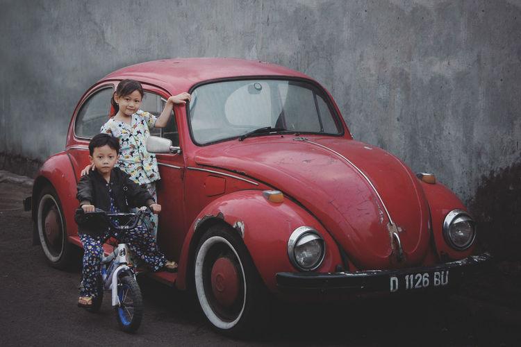 Siblings by vintage car