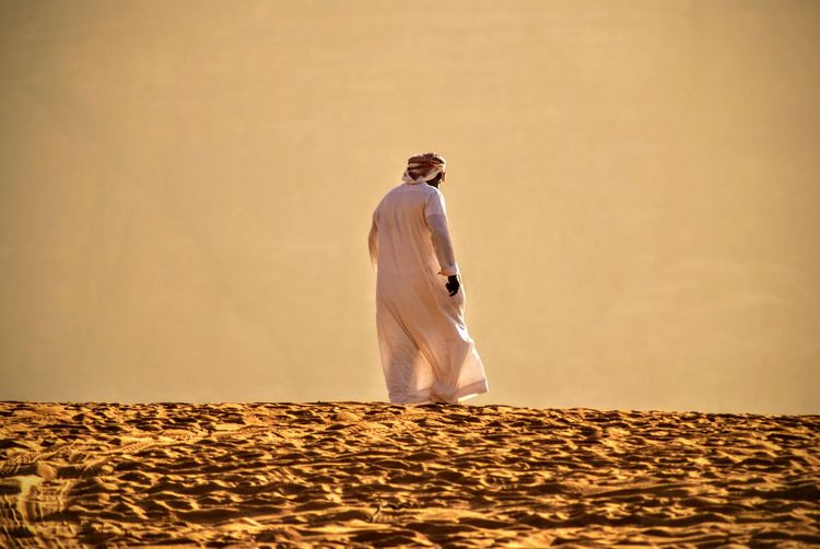 Rear view of man in traditional clothing walking on sand