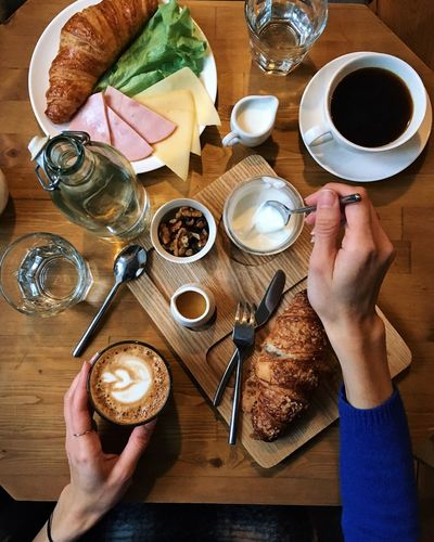Cropped hands of woman eating breakfast on wooden table