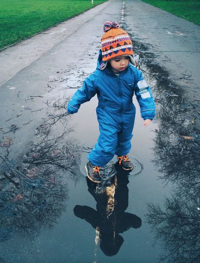 Young boy dancing and splashing in a puddle Carefree Childhood Dancing Dancing Boy Dancing Child Innocence Puddles Rain Rainy Day Real People